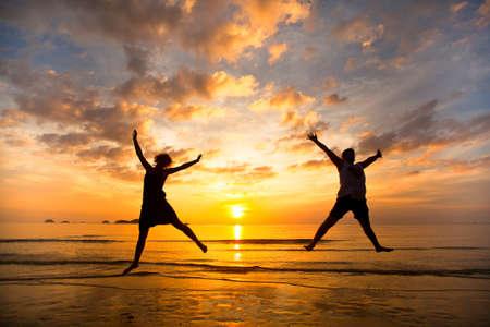 夕暮れ時、海のビーチにジャンプで若いカップル 写真素材