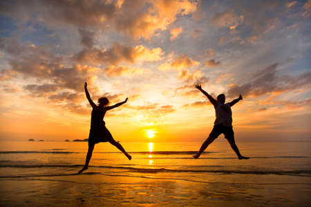 Young couple in a jump on the sea beach at sunset Archivio Fotografico
