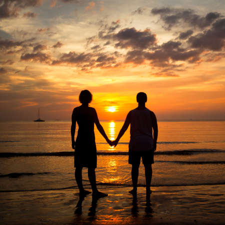 Young couple holding hands on the sea beach at sunset photo