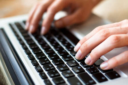 Photo of hands typing text on a laptop keyboard  Stock Photo