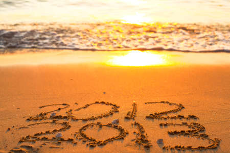 Conceptual photo  New Year 2013 is coming  - inscription 2012 and 2013 on a beach sand photo