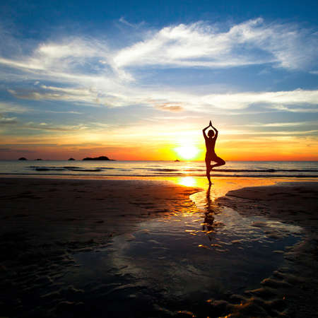 Silhouette of woman practicing yoga on the beach during a beautiful sunset  photo
