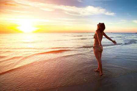 healthy living: A young woman stands on the beach during a beautiful sunset, vacation vitality healthy living concept