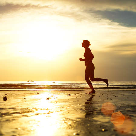 Silhouette of a young woman jogger at sunset on the seashore Stock Photo - 17018090