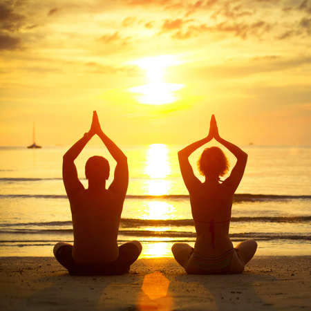 Young couple practicing yoga on the beach at sunset Stock Photo - 17018089