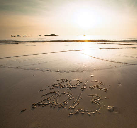 Conceptual  New Year 2013 is coming, inscription 2012 and 2013 on a beach sand photo