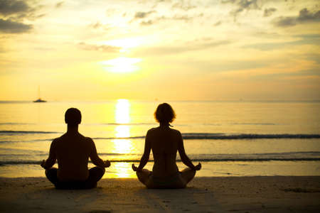 Yoga practice, a young couple sitting on the beach of the sea in the lotus position at sunset  photo