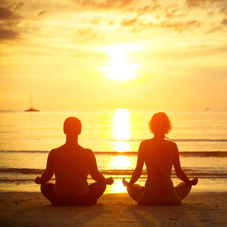 sunrise lake: Young couple in a lotus position meditating on the beach at sunset