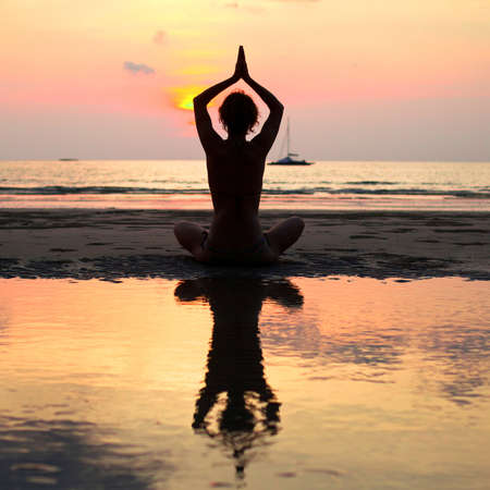 Yoga woman sitting in lotus pose on the beach during sunset, with reflection in water photo
