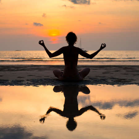Yoga woman sitting in lotus pose on the beach during sunset, with reflection in water. photo