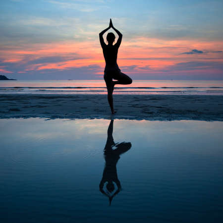yoga beach: Young woman practicing yoga at sunset on the coast, with the reflection in the water