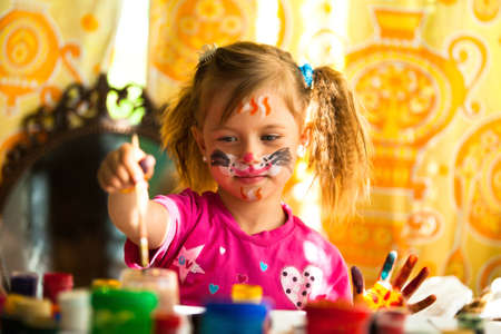 make dirty: Little girl drawing paint with paint of face Stock Photo