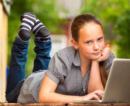Young girl  looking at the camera  lying on the porch of the rural house with a laptop  photo