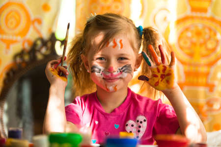 make dirty: Little fanny girl drawing paint with paint of face Stock Photo