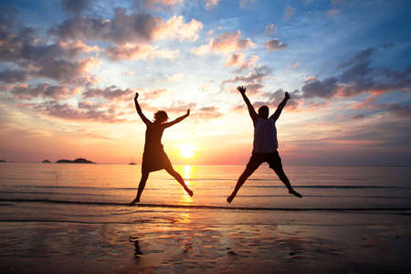 Concept of long-awaited vacation Young couple in a jump on the sea beach at sunset