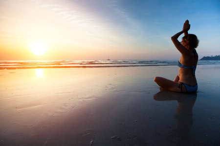 Yoga woman sitting on sea coast at sunset  Stock Photo - 17425357