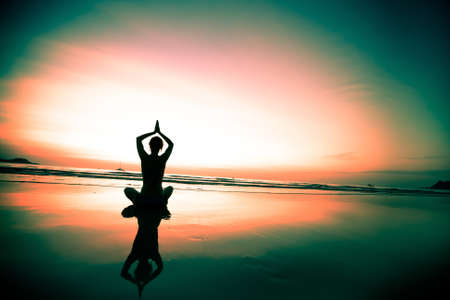 woman meditating on the beach at sunset Stock Photo - 17425359