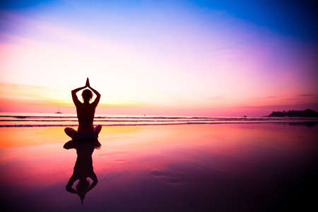 yoga sunset: Silhouette of a woman meditating on the beach at sunset Stock Photo