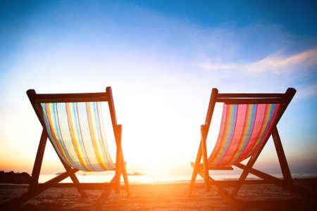 Güneş doğarken ıssız sahil deniz plaj şezlong Çifti, mükemmel tatil konsepti Stock Photo