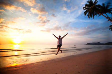Young fun man running on sea beach at sunset photo