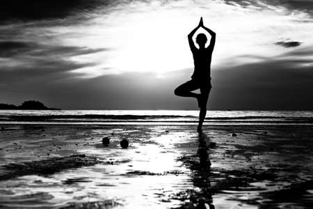 Black and white picture: Young woman practicing yoga on the beach at sunset. photo