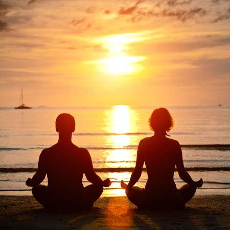 mujer meditando: La pr�ctica del yoga, joven pareja sentada en la playa del mar, en la posici�n de loto al atardecer