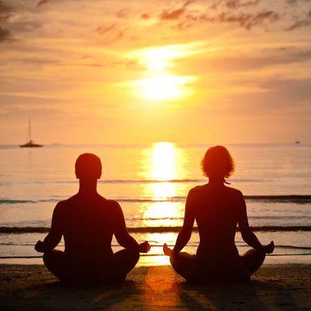 serene people: Yoga practice, young couple sitting on the beach of the sea in the lotus position at sunset Stock Photo