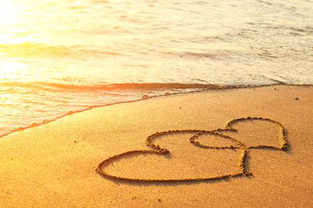 perdonar: Corazones dibujados en la arena de una playa