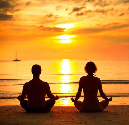 Günbatımında lotus pozisyonunda deniz sahilde oturan genç bir çift, yoga.