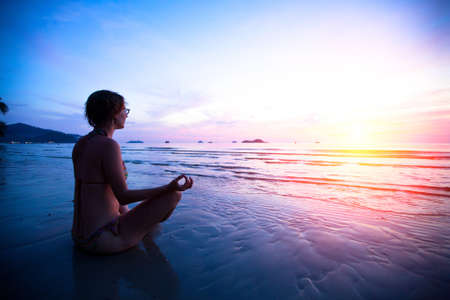 water's edge: Young woman practicing yoga on the beach at sunset