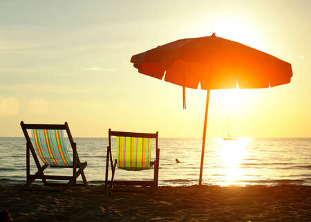 loungers: Pair of beach loungers on the deserted coast sea at sunrise. Stock Photo