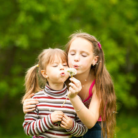11 year old: Cute 5 year old and 11 year old girls blowing dandelion seeds away. Stock Photo