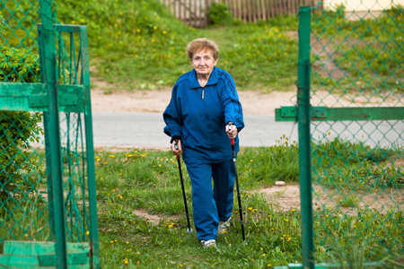 Active old woman nordic walking outdoors, 85 years old. Stock Photo