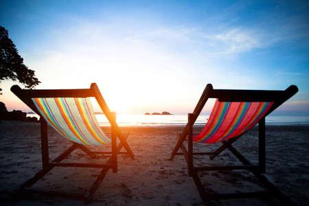 Beach loungers on the deserted coast sea at sunrise. Stock Photo - 17681148