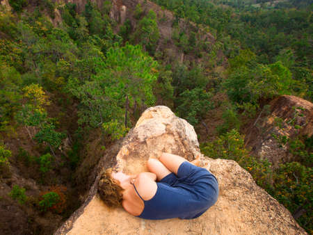 Picture of loneliness - young girl lying on top of the rock in the canyon. Stock Photo - 17567285