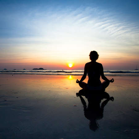 Silhouette yoga woman sitting on sea coast at sunset