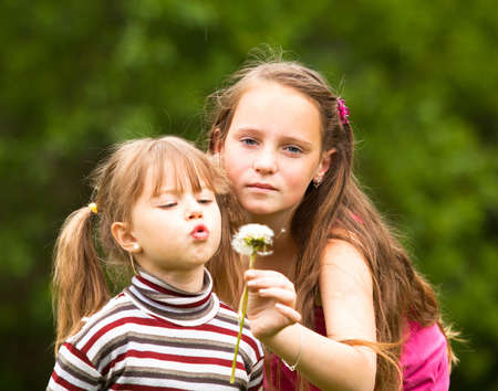 11 year old: Cute 5 year old and 11 year old (looks into the camera) girls blowing dandelion seeds away.