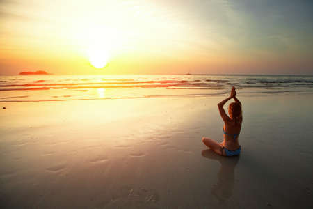 Young woman meditating on the beach at sunset  Stock Photo - 17667779
