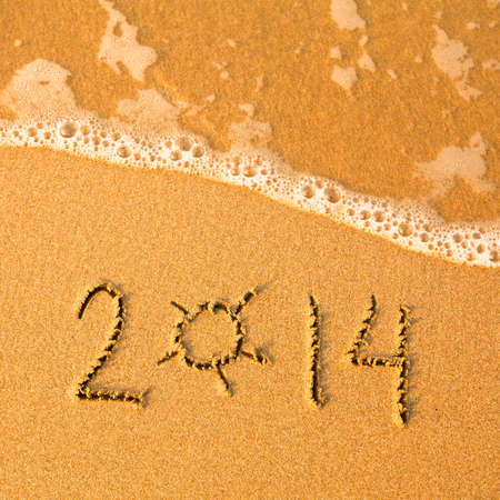 2014 written in sand on beach texture - soft wave of the sea  photo