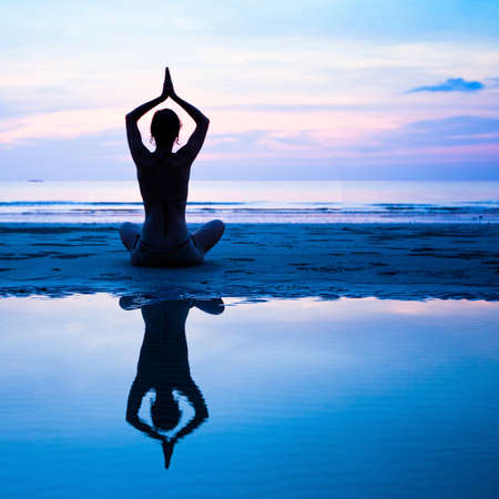 Yoga, harmony of health - silhouette young woman on the beach at sunset  Stock Photo - 17681195