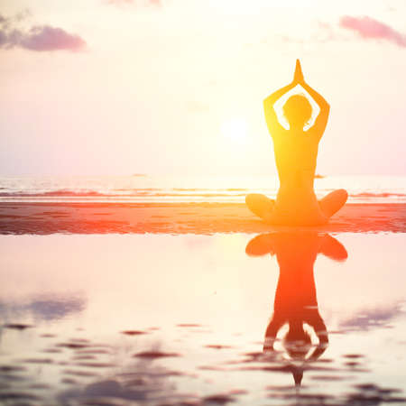 Yoga woman sitting in lotus pose on the beach during sunset, with reflection in water  in bright colors  Stock Photo