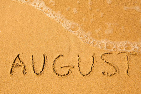 August - written in sand on beach texture - soft wave of the sea  Stock Photo
