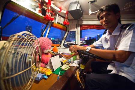 BANGKOK - APRIL 30: Unidentified driver of a water bus plying the Chao Phraya River, Apr 30, 2012 on Bangkok. Fare 10-15 baht, intervals 5 min - does boat attractive alternative ground transportation. Stock Photo - 17838857