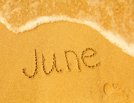 June - written in sand on beach texture - soft wave of the sea  months year series  photo