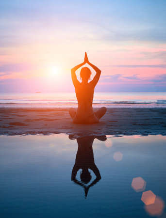 Silhouette of a woman yoga on sea sunset with reflection in water. Stock Photo - 17851874