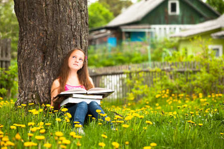 A girl, 11 years old, reads a book in the meadow.