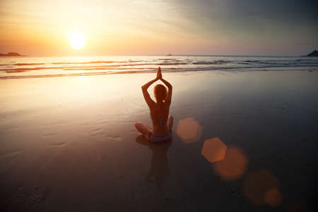 Yoga woman sitting on sea coast at sunset Stock Photo - 17851868
