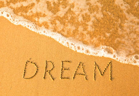 Dream, text written by hand in sand on a beach, with a soft wave. photo