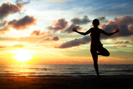 Young woman practicing yoga on the beach during the sunset photo