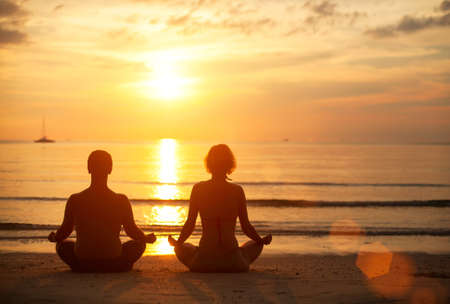 couple lit: A young couple sitting on the beach of the sea in the lotus position at sunset  Yoga practice  Stock Photo